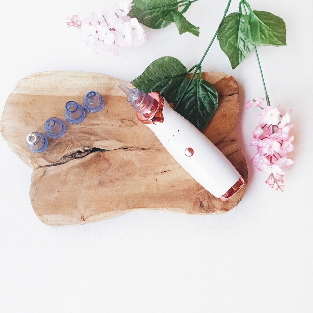 Het huidstofzuigertje (wit met roségoud afwerking) ligt op een houten plankje met één opzetstukje eraan vast. De overige 4 staan netjes op een rij naast het toestel. In de rechterhoek ligt een takje bloesems.