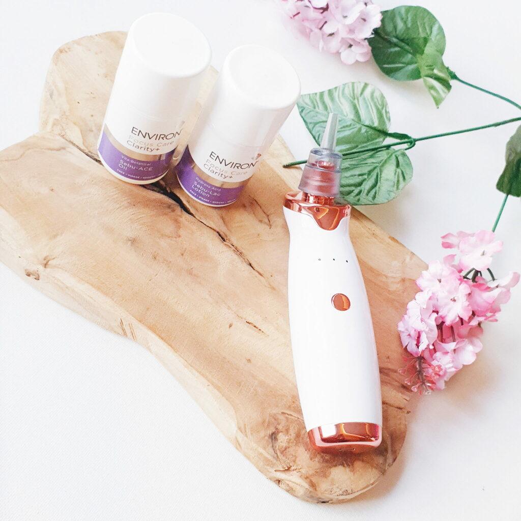 Het huidstofzuigertje ligt op een houten plankje met één opzetstukje eraan vast. Naast het toestelletje staan de huidproducten van Environ. In de rechterhoek ligt een takje bloesems.