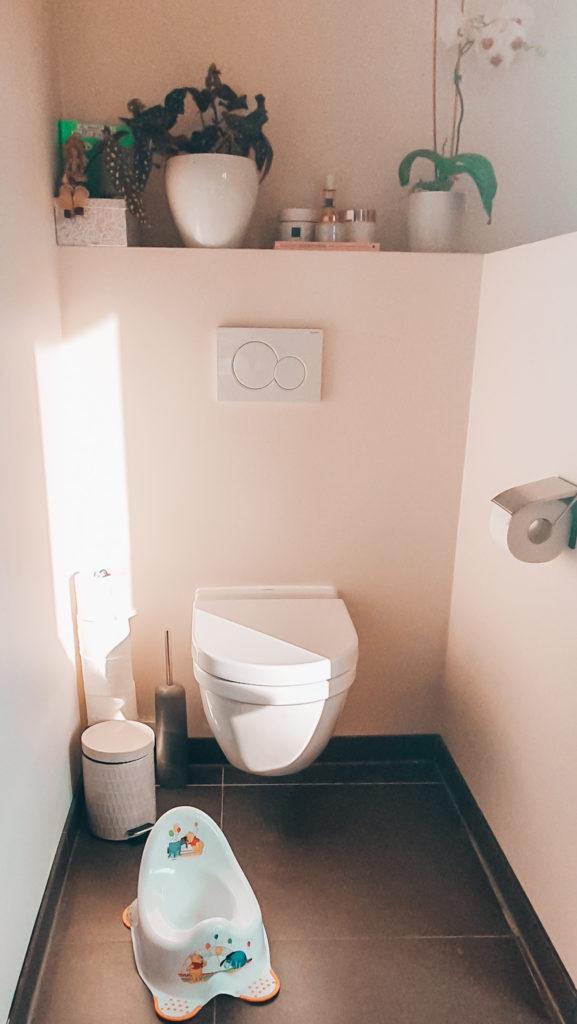 Potjestraining van een een kleuter. Het potje bij de wc. Samen naar WC in de hoop dat hij ons nadoet.